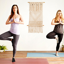 Two models performing yoga pose with stability from professional grip socks