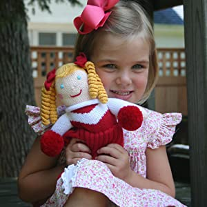 little girl holding a knit red and white cheerleader doll