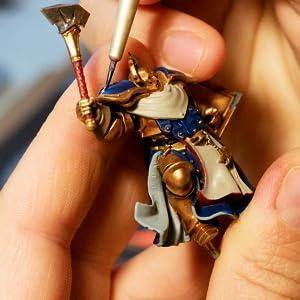 painting warhammer figurine with brush
