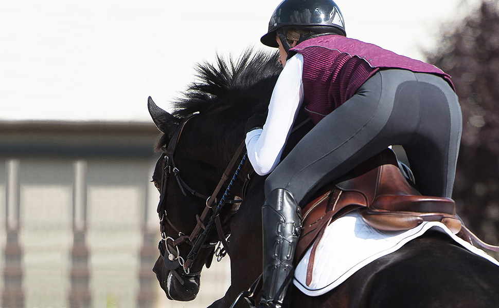 Image from the back of a rider wearing the breeches standing in the stirrups to show the full seat