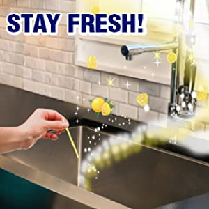 Hand dropping lemon, yellow stick down the drain and lemon cloud bursts are coming out of sink.