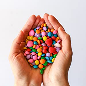 hands holding colorful chocolate candy