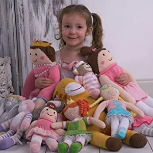 little girl sitting surrounded by several knit zubels brand dolls