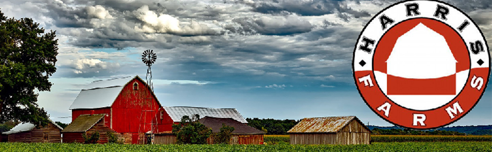 harris farms tree covered barnyard with a beautiful red barn on a farm covered in clouds