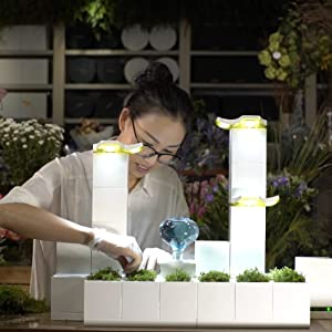 young woman planting plants in a legrow garden with plant and light towers and a humidifier