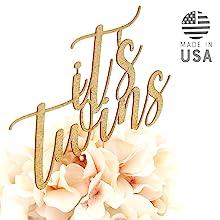 gold it's twins cake topper shown in floral centerpiece arrangement