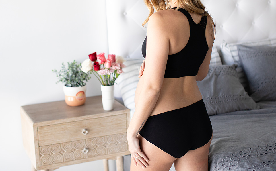 Woman wearing under the bump bikini maternity underwear kneeling on bed