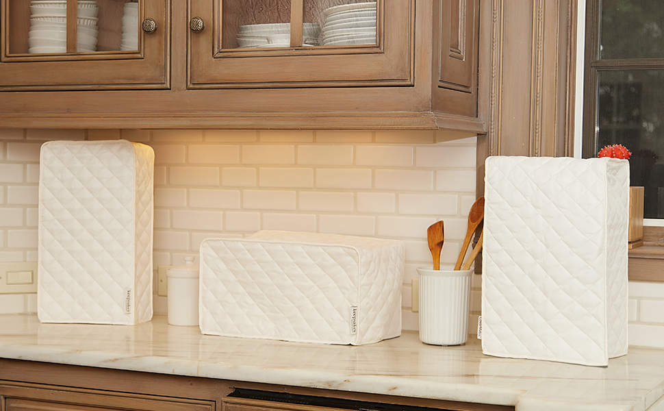 Three white kitchen appliance covers displayed on a counter top