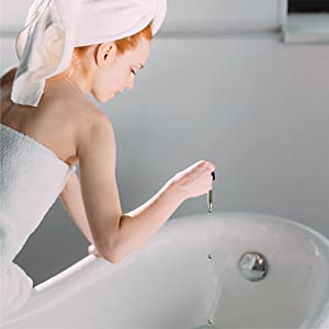 [Image of a womanadding the teatreeoil to her bath]