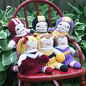 knit football players and cheerleader posed on a red metal chair