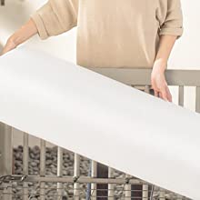 Mom lifting crib mattress in crib
