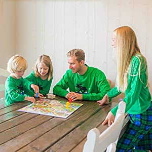 Family playing a board game and wearing matching pajama sets.