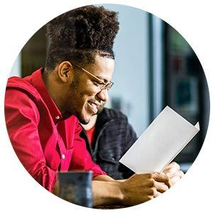 man smiling reading a card
