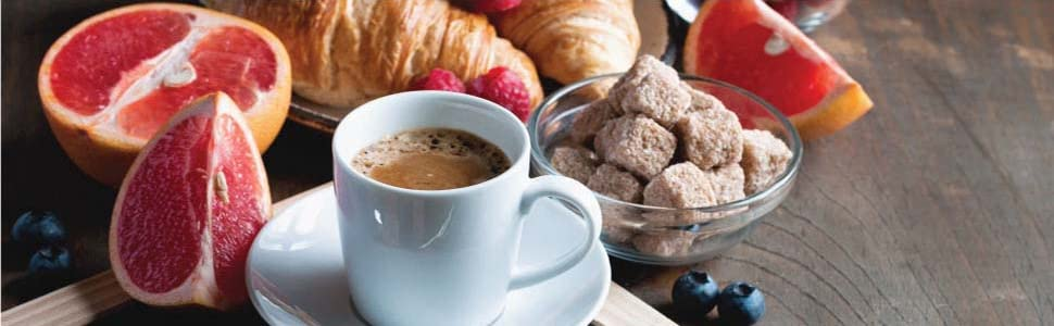 A hot up of coffee surrounded by cereal, grapefruits and croissants.
