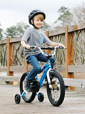 boy riding a blue bike with training wheels