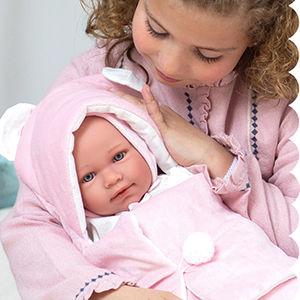 little girl with baby doll swaddled