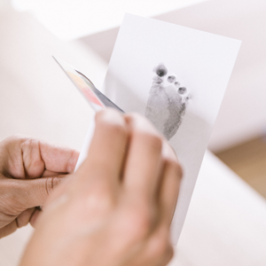 person shown finishing baby's footprint by removing paper from clean touch ink pad