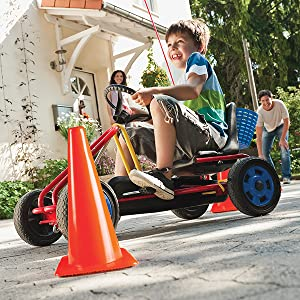 Young boy driving around safety cone in a pedal go cart with parents in background
