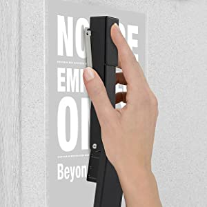 Swingline stapler tacking up a poster to a wall