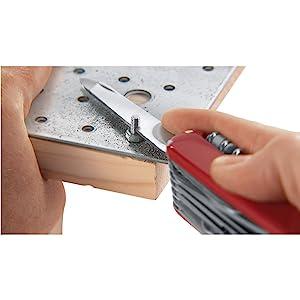 Swiss Army Knife SAK cutting metal on iron and wood with screw