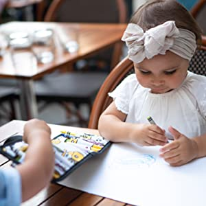 girl drawing at table with urban infant toddler travel crayon wallet set