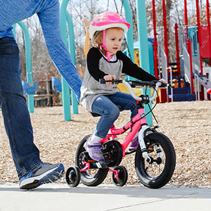 parent pushing a child on a pink bike with training wheels