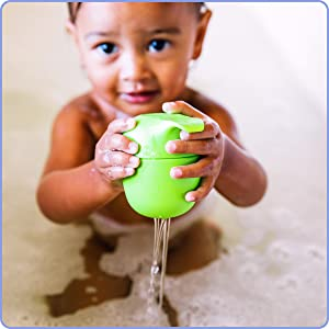 Toddler in bathtub holding green seal toy upside down and water pours down from holes in its head
