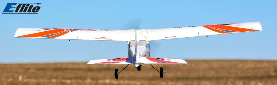 Rear view of E-flite Apprentice STS RC trainer airplane taking off into a blue sky over grassy field