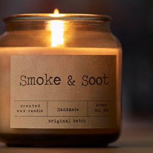 lit candle with the words Smoke & Soot on the label