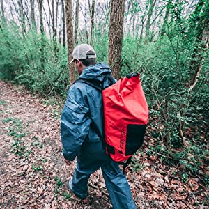 man in rain suit with back pack walking on trail