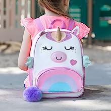 Girl wearing unicorn backpack