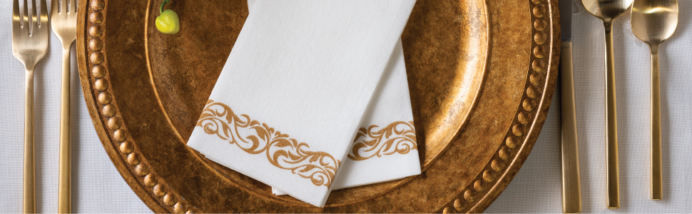 Gold design on white  napkin on plate with cutlery set table