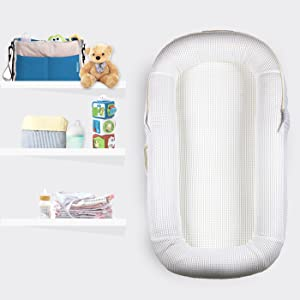 CubbyCove baby lounger in Snow White next to baby toys, teddy bear, baby bottle and baby clothes