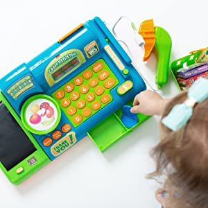 a young girl plays with a blue toy cash register, pretend playing and practicing math skills