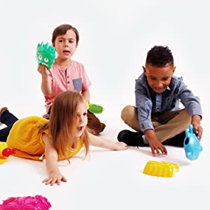 three young diverse and multiethnic kids happily play together with beach sand toys for water