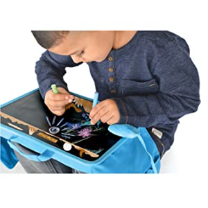 A boy enjoying drawing with his The Piggy Story Lap Desk and chalk set for portable creativity