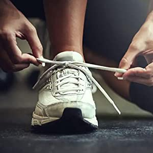 Woman kneeling during a race to tie her shoes