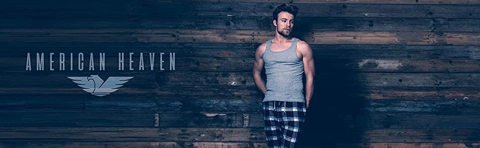 handsome young man wearing lounge pants stands in front of weathered wood wall