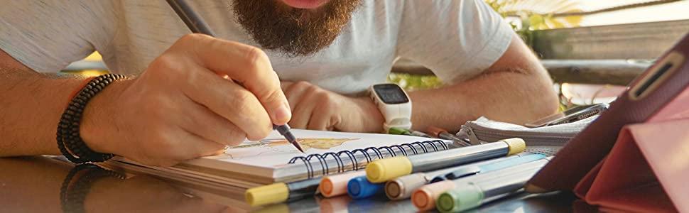 Male designer sketches designs in cafe