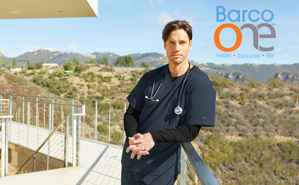 Male Nurse standing outside with mountain view leaning against railing wearing Barco One Mens Scrubs
