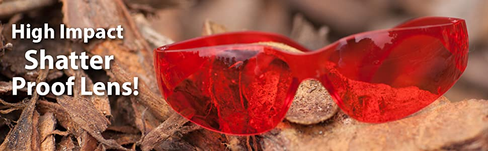Image of red color safety glasses on mulch outdoors.