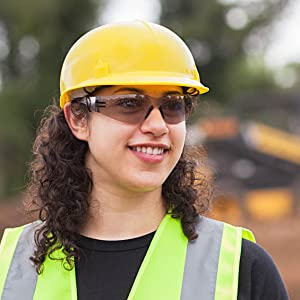 Image of a woman wearing color safety glasses on a worksite.