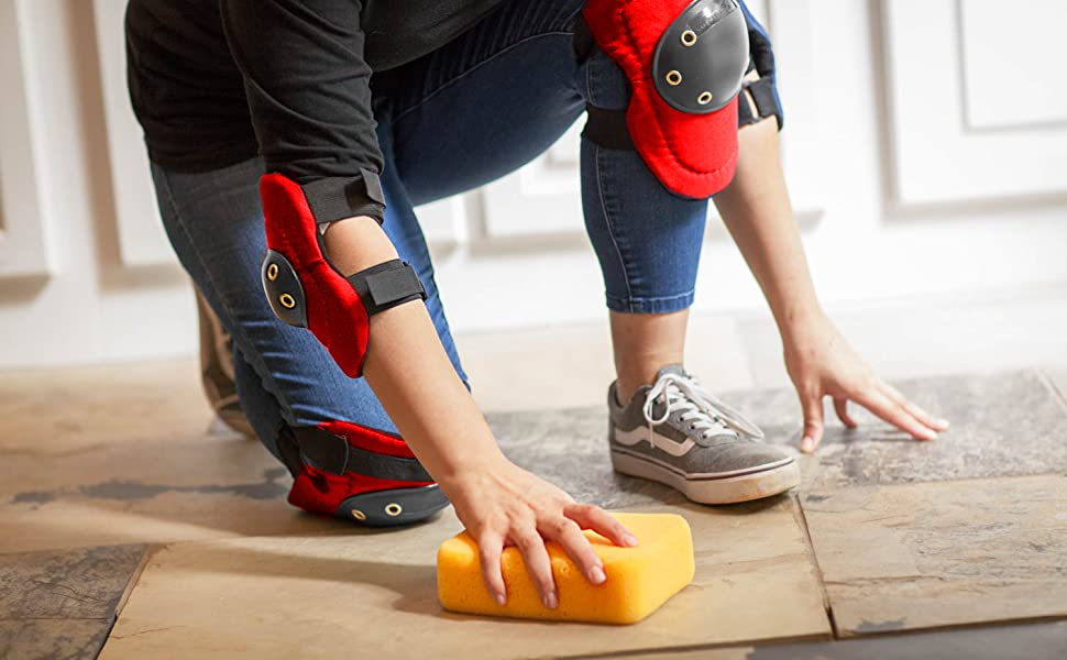 Image of a woman wearing red hard cap elbow and knee pads on tile floor with a grouting sponge.