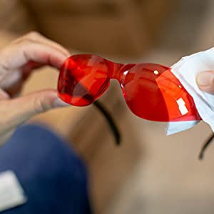 Image of red color safety glasses being wiped down.