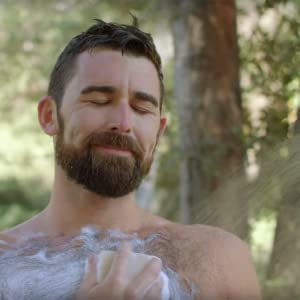 beardy guy scrubbing hairy chest with pine tar soap bar while showering in the woods