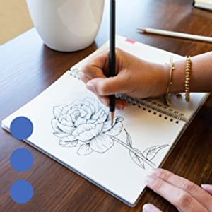 Open notebook with two hands pen sketching a rose, wooden table with white cup in the background