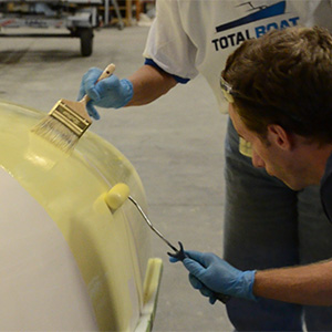 Two people applying TotalBoat Wet Edge Topside Paint using a roller and a paint brush