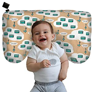 Smiling happy baby propped up with organic cotton nursing pillow in cover printed with pigeons