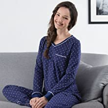 close up of brunette model wearing navy blue and white cotton pajamas seated on a gray couch