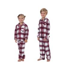 girl and boy wearing fleece plaid matching holiday pajamas